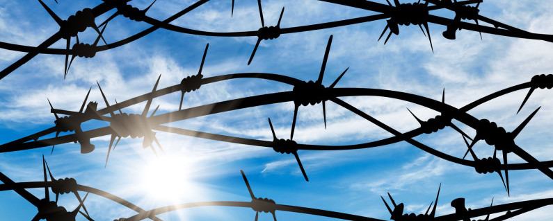 Concept of security. Silhouette of the barbed wire on the background of beautiful sunny sky